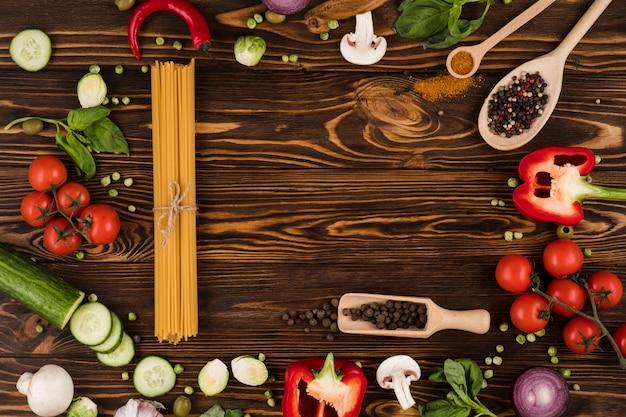 Овощи и макароны на деревянной доске. вид сверху. Premium Фотографии
