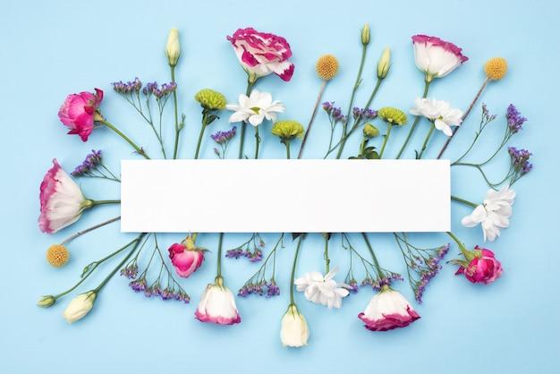 Рама изготовлена из свежих цветов на столе. скопируйте место на пустой пустой белой бумаге Premium Фотографии