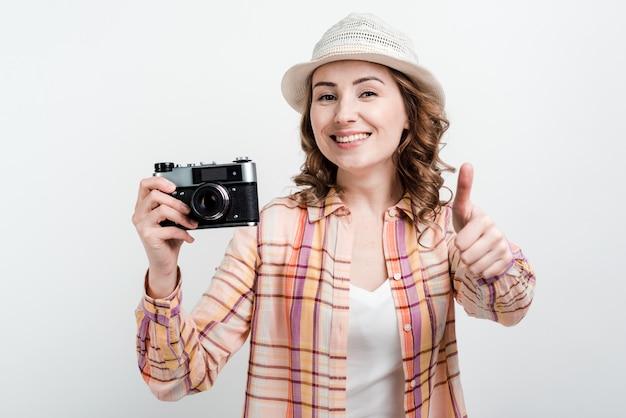 Красотка в шляпе и ретро-камера в руках довольны своей работой, показывая большой палец вверх. Premium Фотографии