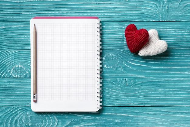 Пустой блокнот для копирования пространство и старинные ручной работы день святого валентина игрушка сердце над светло-голубой деревянный фон Premium Фотографии