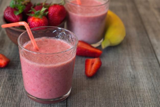 Клубничный молочный коктейль с ягодами и бананом в стеклянной банке Premium Фотографии