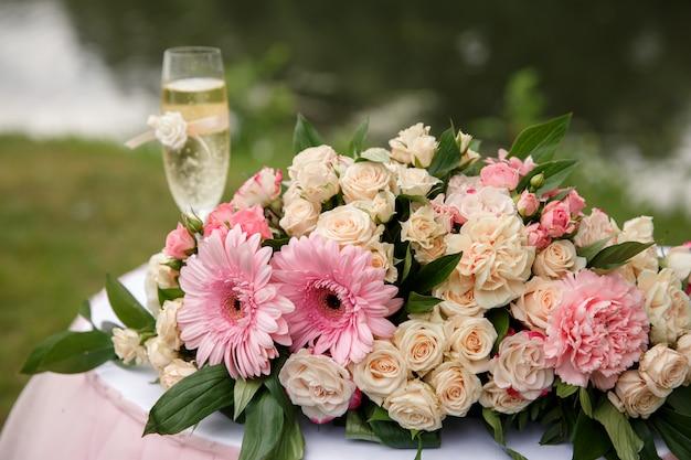 Свадебные цветы и бокал шампанского на столе для свадебной церемонии Premium Фотографии
