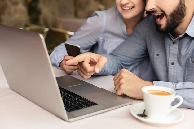 幸せなカップルが自宅で働いて、男と女の屋内でラップトップに取り組んで Premium写真
