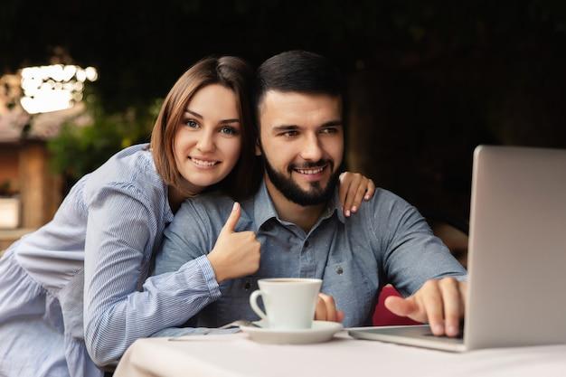 幸せな男と女の家で働いて、屋内でラップトップに取り組んでいる一杯のコーヒーと若いカップル Premium写真