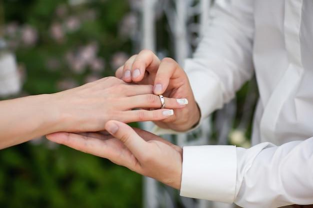リング。結婚指輪。新しい幸せな家族の創造を象徴する、結婚指輪を交換する厳粛なプロセスでの新郎新婦の手。 Premium写真