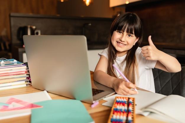 オンライン学習。家で勉強して幸せな女の子。教育と遠隔学習。 Premium写真