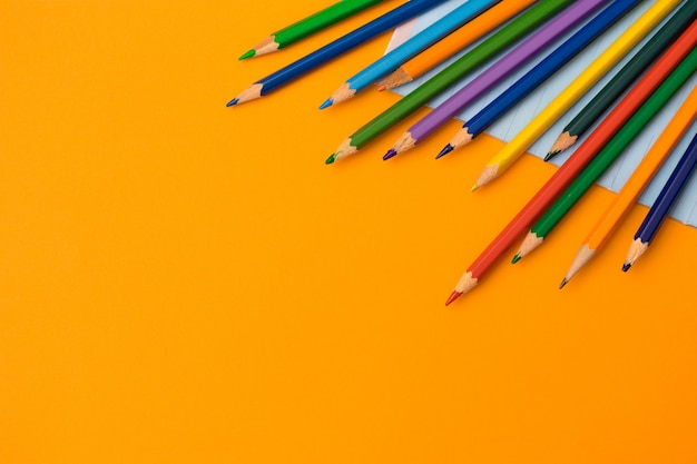 Цветные карандаши и тетрадь на оранжевом фоне. обратно в школу концепции плоской планировки. Premium Фотографии