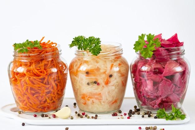 発酵して保存されたベジタリアン料理のコンセプト。ザワークラウト、赤キャベツのマリネ、にんじんの開いたガラスの瓶 Premium写真