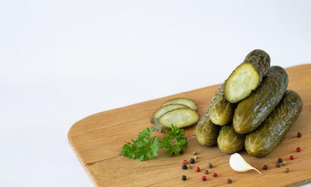 健康的な発酵スライスガーキンやキュウリのハーブとスパイスを白で隔離される素朴な木の板に Premium写真