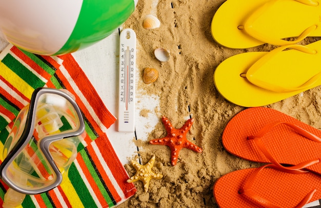 砂浜でビーチサンダル、ボール、貝殻、ヒトデ Premium写真