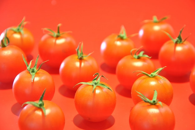 赤い背景にいくつかのチェリートマト Premium写真