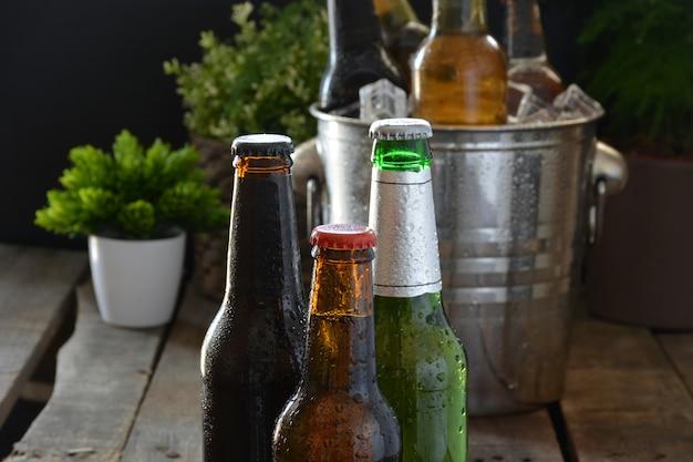 木のテーブルにさまざまなビール。それらを冷たく保つために氷が付いているびんそしてガラスがあります Premium写真