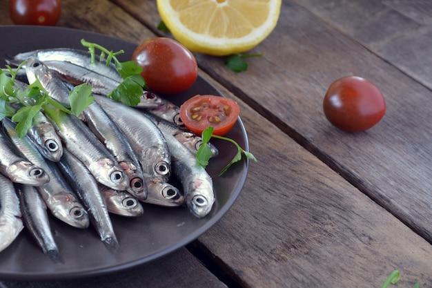 Свежие анчоусы на деревянном столе в сопровождении масла, помидоров и петрушки Premium Фотографии
