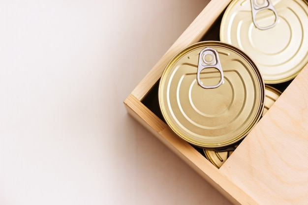 Жестяные банки в коробке. разнообразие консервов в полных жестяных банках. настоящие консервы. вид сверху. выборочный фокус. Premium Фотографии