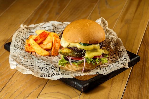 クラフトビーフハンバーガーとフライドポテトの木製テーブル Premium写真
