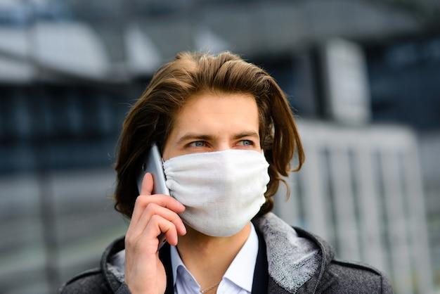 Молодой человек в медицинской маске снаружи, без денег, кризиса, бедности, лишений. карантин, коронавирус, изоляция. Premium Фотографии