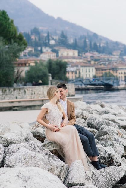 Сало, италия. романтическая молодая пара, сидя на скамье подсудимых Premium Фотографии