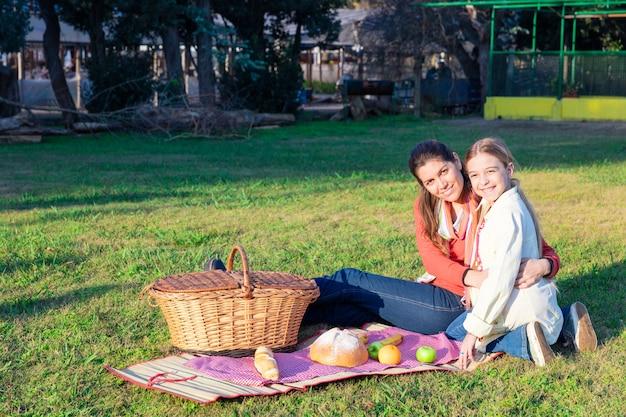 公園でピクニック母と娘 無料写真