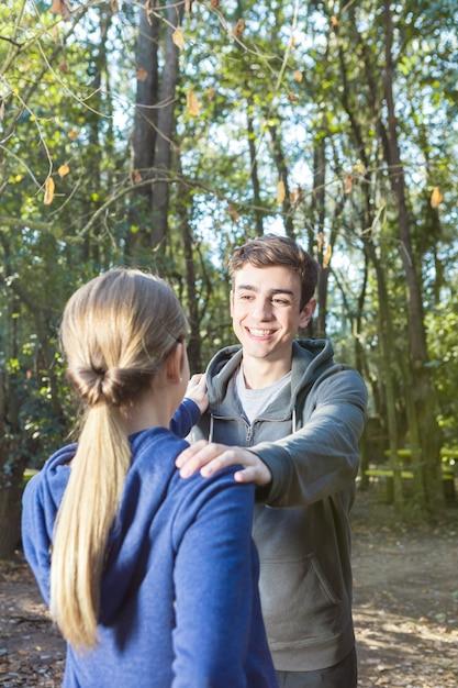 森の中で彼のガールフレンドとのウォームアップを行って愛らしいボーイフレンド 無料写真