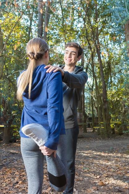 健康なカップルが公園で実行した後、ストレッチ体操をしています 無料写真