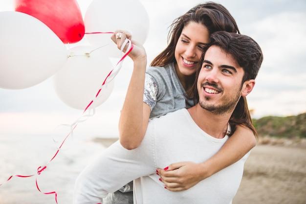 彼女のボーイフレンドが彼女の背中に彼女を運びながら、少女は風船と笑顔 無料写真