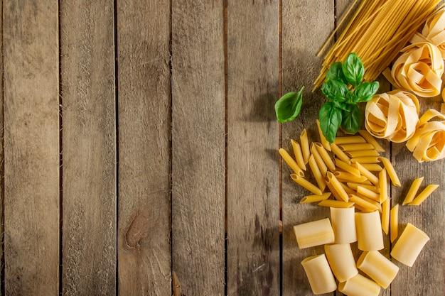 イタリアのパスタ、バジルと木製の背景 無料写真