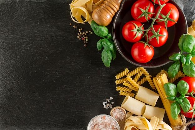 Композиция с различными макаронными изделиями, помидоры и базиликом на темной поверхности Бесплатные Фотографии