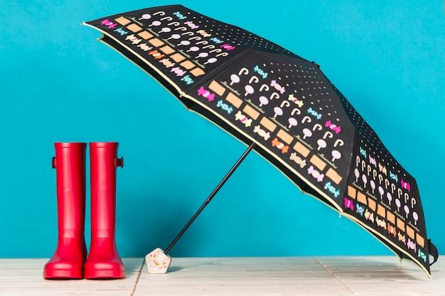 オープン傘の横に赤い水のブーツ 無料写真
