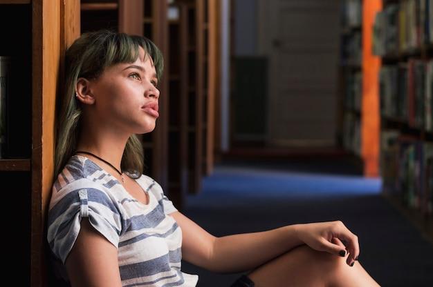 本棚に傾いている思慮深い女の子 無料写真