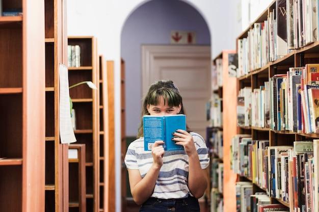 書籍の後ろに隠れている図書館の少女 無料写真