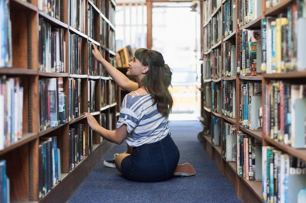 ライブラリーの本を探している少女 無料写真