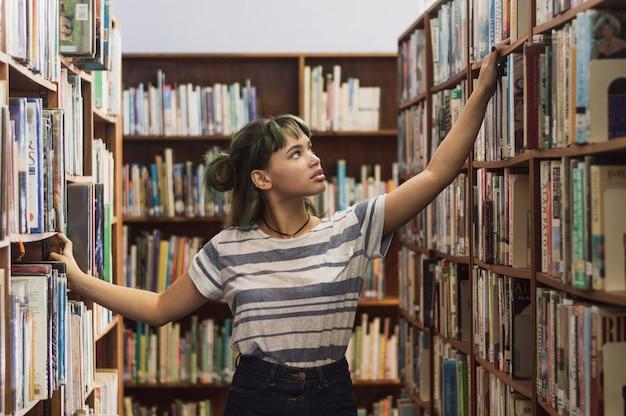 本棚で本を探している少女 無料写真