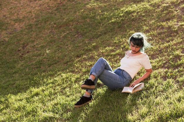 日当たりの良い丘で読書する女の子 無料写真