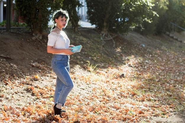 晴れた丘の本を持つ少女 無料写真