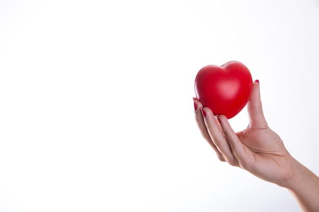 Рука с красным пластиковым сердцем Бесплатные Фотографии