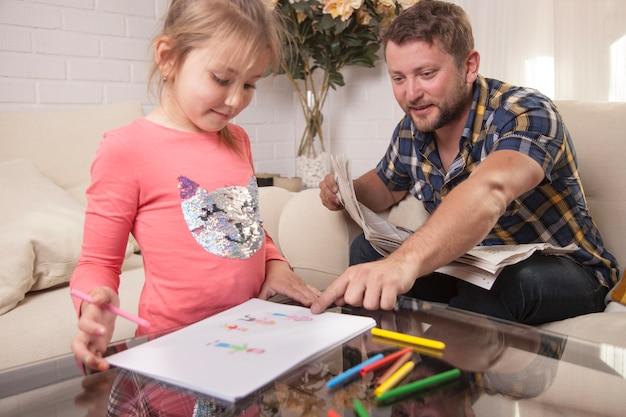 娘の絵を指している若い父親 無料写真