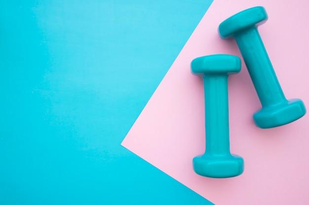 青とピンクの背景にダンベル 無料写真