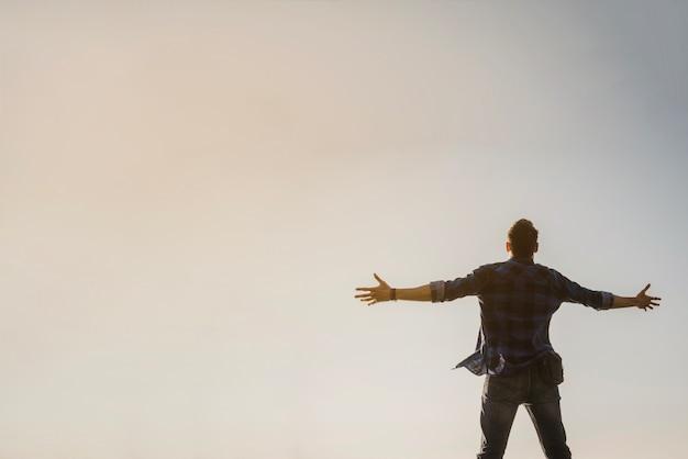 空を見る開いた武器を持つ男 無料写真