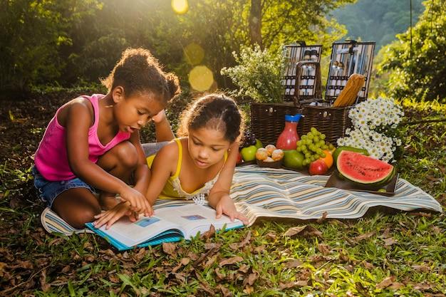 Две девочки, читающие на ткани для пикника Бесплатные Фотографии