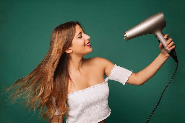 かわいい女の子は彼女の髪を乾燥させる 無料写真