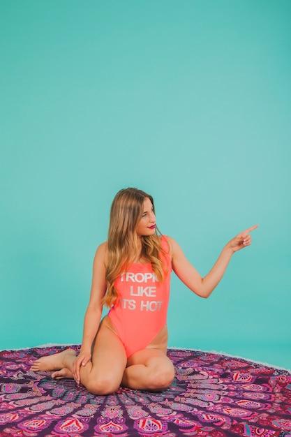 彼女の左を指している水着の女の子 無料写真