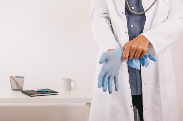 Профессиональный врач в перчатках в своем кабинете Бесплатные Фотографии