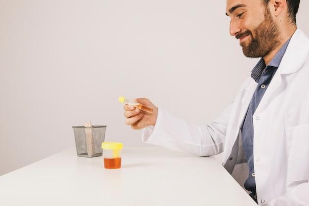 彼の机の上で尿検査をするスマイリー医 無料写真