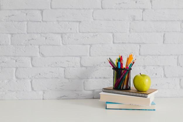 テーブル上の本、リンゴ、鉛筆 無料写真