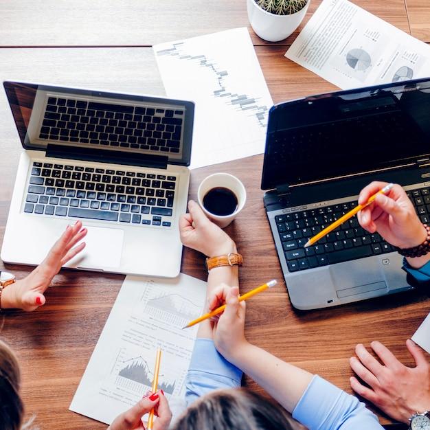 Люди, сидящие на столе с ноутбуками, работающими Бесплатные Фотографии