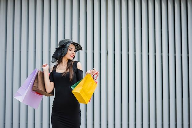 Девушка в черном платье с сумками Бесплатные Фотографии