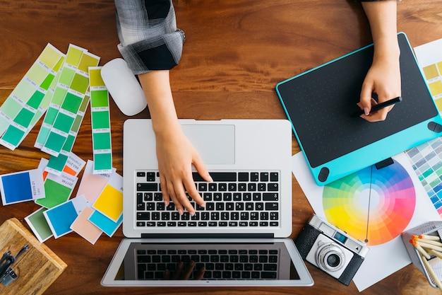グラフィックタブレットとラップトップを使用しているグラフィックデザイナーのトップビュー 無料写真