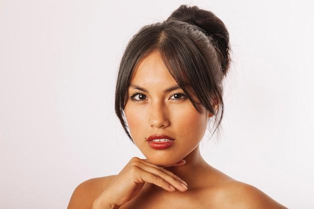 興味深い若い女性は、顎の下で手を使ってポーズを取る 無料写真