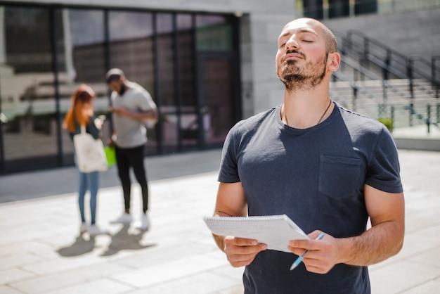 メモ帳の瞑想の外に立っている男 無料写真