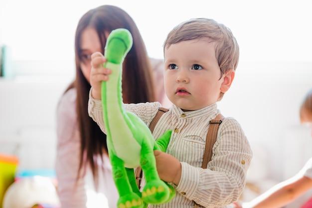 緑の恐竜のおもちゃを持っている小さな男の子 無料写真